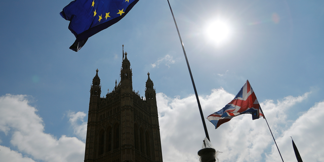 FILE  - In this Thursday, April 11, 2019 file photo, protestor flags fly opposite the Houses of Parliament in London. The British economy is likely to weaken as firms stop ease up on Brexit preparations now that Britain's departure from the European Union has been delayed by months, the Bank of England said Thursday, May 2, 2019. (AP Photo/Frank Augstein, File)