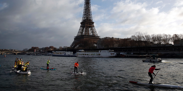 FILE - In this Dec.9, 2018 file photo, competitors paddle on the Seine river in front of the Eiffel Tower in Paris. The Eiffel Tower press office said Monday May 20, 2019 an unidentified individual tried to scale the near-300 meter (near-328 yard) monument on Monday afternoon but it wasn't clear how high the climber managed to get. (AP Photo/Christophe Ena, File)