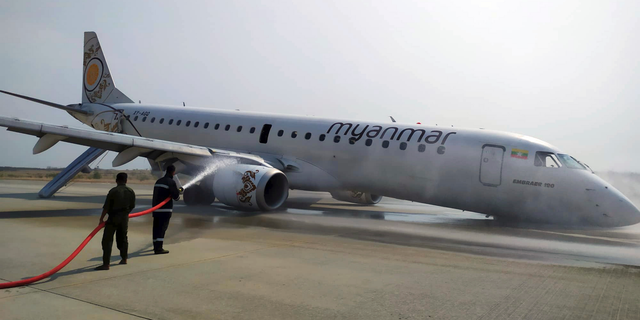 Firefighters work with hose on a plane of Myanmar National Airline (MNA) after an accident at Mandalay International airport Sunday, May 12, 2019, in Mandalay, Myanmar. All passengers and crew are reported safe and uninjured after a Myanmar National Airlines plane made a scheduled but emergency landing at Mandalay International Airport on only its rear landing wheels after the front landing gear failed to deploy.