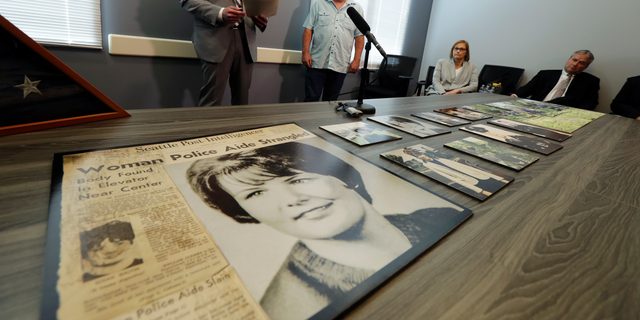 Seattle Police homicide Detective Rolf Norton, left, talks to reporters near a photo of Susan Galvin, who was murdered in Seattle in 1967, Tuesday, May 7, 2019, at Seattle Police Dept. headquarters in Seattle. Police said Tuesday they have solved the cold case of the murder of Galvin with the help of DNA and a family tree -- a method that has revolutionized cold-case investigations across the U.S. Looking on is Galvin's brother, Chris Galvin, center. (AP Photo/Ted S. Warren)