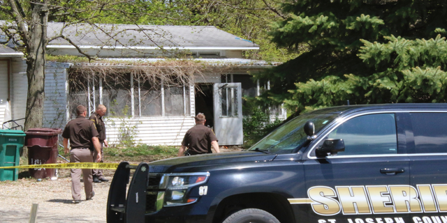 In this Monday, May 6, 2019 photo, St. Joseph County Sheriff deputies stand outside the site where a woman was fatally shot in Fawn River Township, Mich. Authorities say a 9-year-old is suspected in the shooting of a woman in her southern Michigan home. (Corky Emrick/Sturgis Journal via AP)