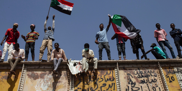 Sudanese protesters wave national flags at the sit-in outside the military headquarters, in Khartoum, Sudan, Thursday, May 2, 2019. Sudan's protesters are holding a mass rally to step up pressure on the military to hand power to civilians following last month's overthrow of President Omar al-Bashir. (AP Photos/Salih Basheer)