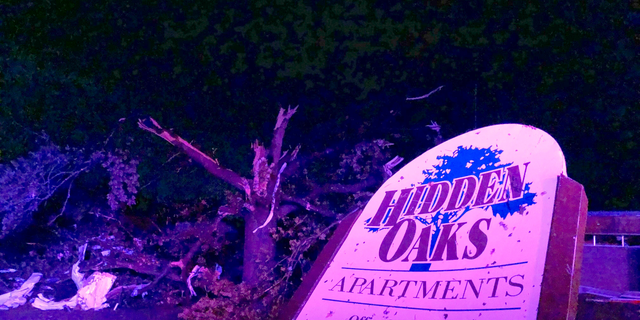 The sign for the Hidden Oaks residential complex in Jefferson City, Missouri, is bent after a violent tornado has touched down.