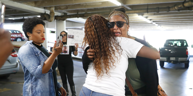 "Brittany Bowens, facing camera, the mother of the missing 4-year-old, Meleah Davis is hugged by Taneshia Brown, after protesters demanding ""Justice for Meleah"", followed Bowens down the street and confronted her in a parking garage, after the court postponed a court appearance for Derion Vence, who is charged with tampering with evidence in the case of Meleah Davis' disappearance, Monday, May 13, 2019, in Houston. Brown, one of the protesters handed Bowens a poster, and said later, ""It's like someone failed you (Bowens) and you failed your baby. It's hurtful."" (Karen Warren/Houston Chronicle via AP)"