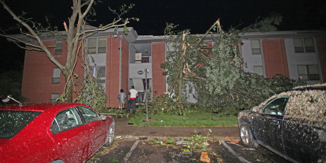 Residents walk toward their Westbrooke Village Apartment building that was heavily damaged by a tornado Tuesday morning, May 28, 2019, in Dayton, Ohio.