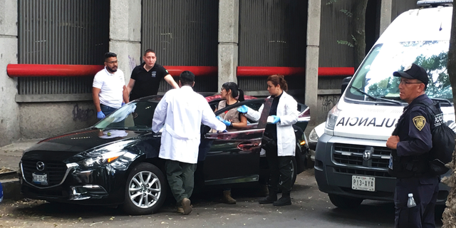 Forensic investigators examine a vehicle after the bodyguard of prominent Mexican journalist Héctor de Mauleón repelled an assault, in Mexico City, Monday, May 6, 2019. One man was killed in the attack and It was not immediately clear if de Mauleón was targeted or if it was an attempted carjacking. (AP Photo/Peter Orsi)