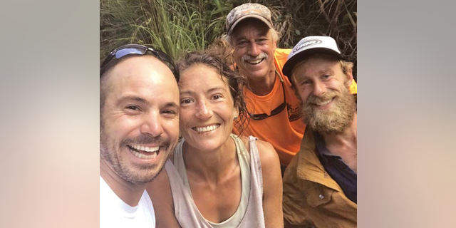 In this Friday,, photo provided by Troy Jeffrey Helmer, resident Amanda Eller, second from left, poses for a photo after being found by searchers, Javier Cantellops, far left, Helmer and Chris Berquist above the Kailua reservoir in East Maui, Hawaii, on Friday afternoon. The men spotted Eller from a helicopter and went down to retrieve her. She was taken to the hospital and was in good spirits, her family said. Eller had been missing since May 8.