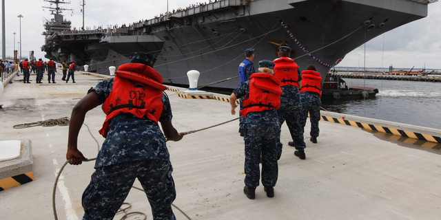 """FILE - In this Aug. 7, 2012, file photo, Navy shore crew haul in lines as the nuclear powered aircraft carrier USS Abraham Lincoln arrives at Naval Station Norfolk in Norfolk, Va. The U.S. is dispatching the USS Abraham Lincoln and other military resources to the Middle East following """"clear indications"""" that Iran and its proxy forces were preparing to possibly attack U.S. forces in the region, according to a defense official on May 5, 2019. (AP Photo/Steve Helber, File)"""