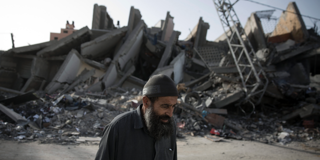 An elderly Palestinian man walks next to the rubble of multi-story building was hit and destroyed on Sunday by Israeli airstrikes, in Gaza City, Monday, May. 6, 2019. The Israeli military has lifted protective restrictions on residents in southern Israel while Gaza's ruling Hamas militant group reported a cease-fire deal had been reached to end the deadliest fighting between the two sides since a 2014 war. (AP Photo/Khalil Hamra)