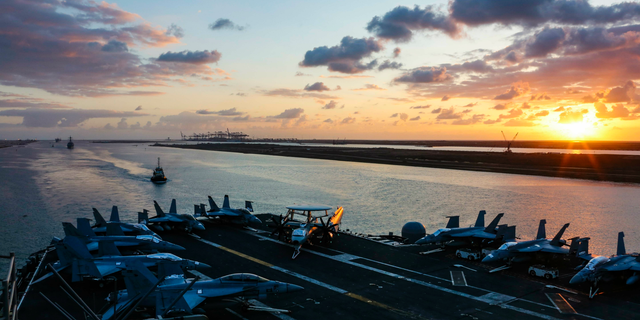 In this Thursday, May 9, 2019 photo released by the U.S. Navy, the Nimitz-class aircraft carrier USS Abraham Lincoln transits the Suez Canal in Egypt. The aircraft carrier and its strike group are deploying to the Persian Gulf on orders from the White House to respond to an unspecified threat from Iran. (Mass Communication Specialist Seaman Dan Snow, U.S. Navy via AP)