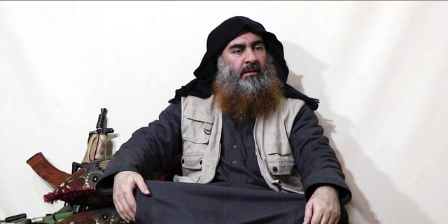 """This file image made from video posted on a militant website Monday, April 29, 2019, purports to show the leader of the Islamic State group, Abu Bakr al-Baghdadi, being interviewed by his group's Al-Furqan media outlet. No longer burdened by territory and administration, Islamic State group leader Abu Bakr al-Baghdadi outlined the new path forward for his group: Widen your reach, connect with far-flung militant groups and exhaust your enemies with a """"war of attrition."""" (Al-Furqan media via AP, File)"""