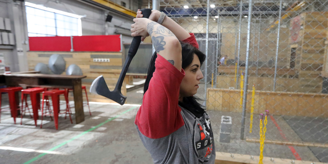 "General manager Devan Watanabe throws an axe at Social Axe Throwing Wednesday, May 1, 2019, in Salt Lake City. The Utah Department of Alcoholic Beverage Control announced Tuesday, April 30, 2019, that beer will not be allowed at a Salt Lake City karaoke business or an Ogden ax-throwing venue because neither fits the 14 definitions of a ""recreational amenity,""under a new law passed by Utah's Republican-controlled legislature during the yearly session that ended in March. (AP Photo/Rick Bowmer)"