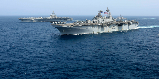 """CORRECTS DATE - In this Friday, May 17, 2019, photo released by the U.S. Navy, the amphibious assault ship USS Kearsarge sails in front of the USS Abraham Lincoln aircraft carrier in the Arabian Sea. Commercial airliners flying over the Persian Gulf risk being targeted by """"miscalculation or misidentification"""" from the Iranian military amid heightened tensions between the Islamic Republic and the U.S., American diplomats warned Saturday, May 18, 2019, even as both Washington and Tehran say they don't seek war. (Mass Communication Specialist 1st Class Brian M. Wilbur, U.S. Navy via AP)"""