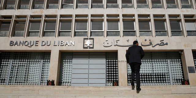 FILE - This Tuesday, Jan. 22, 2019 file photo, a man heads to the Lebanese central bank, in Beirut, Lebanon. The Beirut Stock Exchange said Monday, May 6, 2019, that it is suspending trading due to the open strike declared by the employees of Lebanon's central bank. Hundreds of Lebanese public employees are on strike amid concerns that their salaries and benefits might be cut as the government discusses an austerity budget. (AP Photo/Hussein Malla, File)