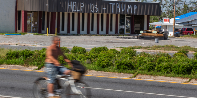 In this May 3, 2019 photo, a cyclist rides by a building damaged by Hurricane Michael in Parker, Fla. Residents in these parts of the Florida Panhandle that were devastated by Hurricane Michael six months ago hope President Donald Trump gets a glimpse of the continuing suffering in the region when he arrives for a campaign rally this week. (AP Photo/Mike Fender)