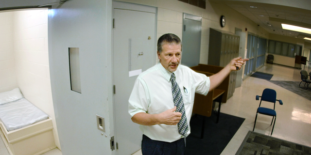In this May 2018 photo,  Tim Tausend, director of the North Dakota Youth Correctional Center, shows a look inside one of the dorm rooms inside the 25-bed Pine Cottage for high-risk male juveniles in Mandan, N.D. Authorities have charged four teenagers, including one from South Dakota, with multiple felonies in adult court in what they described as a riot earlier this year at North Dakota's youth prison. (Mike McCleary/The Bismarck Tribune via AP)