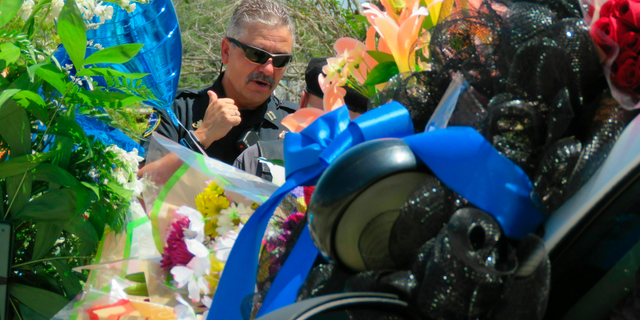 A Biloxi police vehicle that was assigned to patrolman Robert McKeithen is covered in flowers as Biloxi Police Capt. Milton Houseman, rear, talks , with a member of the Combat Veterans Motorcycle Association, Tuesday, May 7, 2019, in Biloxi, Moss. Houseman said he was one of the officers who brought Darian Tawan Atkinson, 19, to Biloxi after his arrest in Wiggins on May 6, in the death of Patrolman McKeithen. (AP Photo/Janet McConnaughey)