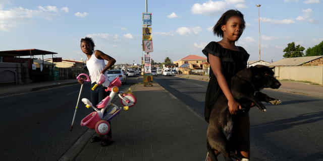 A young girl carries her dog as she crosses the main road, with headline from a newspaper and election posters on the streets of Soweto, South Africa, Friday, May 10, 2019. The ruling African National Congress is coasting to a comfortable lead in South Africa's presidential and parliamentary elections with 80% of the vote counted, but the ongoing tally shows the party getting less support than in the previous poll five years ago. (AP Photo/Themba Hadebe)