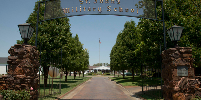 FILE - This June 27, 2012, file photo, shows the the entrance to St. John's Military Academy in Salina, Kan. Nearly seven months before publicly announcing its plans to close, the embattled Kansas military school amended its articles of incorporation to remove the Episcopalian church that founded it from receiving its property upon its demise. The Episcopalian boarding school announced in February it planned to shut down after its May 11 commencement. The 131-year-old school said education has changed dramatically, resulting in lower enrollment and unsustainable higher costs. (AP Photo/Orlin Wagner, File)