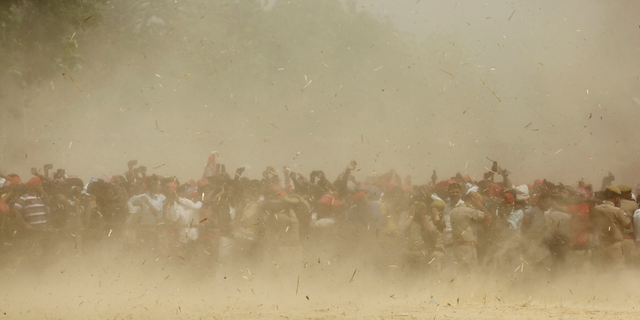 Supporters of Samajwadi Party president Akhilesh Yadav are seen through dust as a helicopter carrying Yadav lands at an election rally venue in Prayagraj, Uttar Pradesh, India, Sunday, May 5, 2019. With 900 million of India's 1.3 billion people registered to vote, the Indian national election is the world's largest democratic exercise. (AP Photo/Rajesh Kumar Singh)