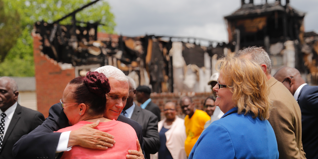 Vice President Mike Pence hugs a congregation member as he visits pastors and congregation at the Mt. Pleasant Baptist Church, which was burned along with two other nearby African American churches, in Opelousas, La., Friday, May 3, 2019. Holden Matthews, who is white, was arrested for arson and other charges in relation to the church burnings. (AP Photo/Gerald Herbert)