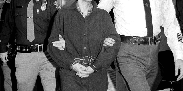 FILE - In this Nov. 24, 1981, file photo, Weather Underground member Judith Clark is handcuffed as she is escorted into Rockland County Courthouse in New City, N.Y. State prison officials say Clark was released Friday, May 10, 2019, from Bedford Hills Correctional Facility in Westchester County. She became eligible for parole consideration after Gov. Andrew Cuomo granted her clemency in 2016, citing her many achievements in prison. (AP Photo/David Handschuh, File)