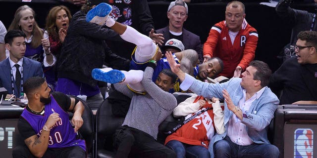Drake, bottom left, watches as Golden State Warriors guard Andre Iguodala dives into the crowd during the first half of Game 1 of the basketball's NBA Finals against the Toronto Raptors, Thursday, May 30, 2019, in Toronto. (Associated Press)