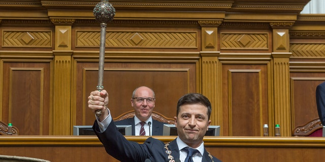 The new Ukrainian President Volodymyr Zelenskiy holds up a mace, the Ukrainian symbol of power, during his inauguration ceremony in Kiev, Ukraine, Monday, May 20, 2019. (Andrii Nesterenko, Ukrainian Parliament Press Service via AP)