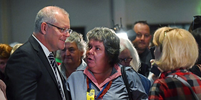 Australian Prime Minister Scott Morrison, left, talks with attendees at the Country Women's Association NSW annual conference after he was hit on the head with an egg during a protest at the event.