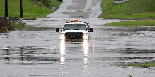 A pickup truck drives on a flooded street in Enid, Okla.(Billy Hefton/The Enid News & Eagle via AP)