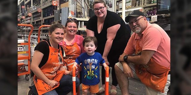 Two-year-old Logan Moore with some of the Home Depot employees who built his walker (Facebook/Jeffrey Anderson)