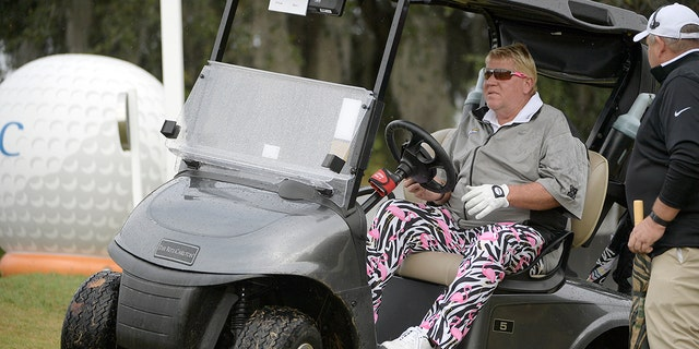 John Daly drives in his cart after striking a hole in the tenth hole during the first round of the Father Son Challenge golf tournament in Orlando, Florida.