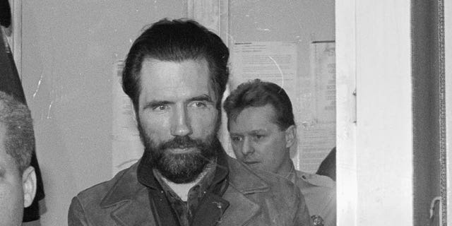 """(Original Caption) Philadelphia: Gary Heidnik, accused """"House of Horrors"""" killer, is escorted to court here 4/1 where his preliminary hearing was delayed until next week so he could have time to hire an attorney and officials would have more time to consolidate charges against the self-styled preacher."""