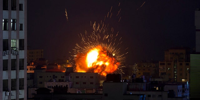 An explosion caused by an Israeli airstrike on a building in Gaza City, Saturday, May 4, 2019. (AP Photo/Khalil Hamra)