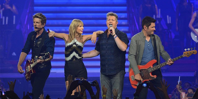 Taylor Swift is joined onstage by special guests (L-R) Joe Don Rooney, Gary LeVox and Jay DeMarcus of Rascal Flatts as she wraps the North American portion of her RED tour playing to a crowd of more than 14,000 fans on the second of three sold-out hometown shows at Nashville's Bridgestone Arena on Sept. 20, 2013. (Photo by Larry Busacca/TAS/Getty Images for TAS)