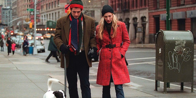 John F. Kennedy Jr. and his wife Carolyn walk with their dog on January 1, 1997, in New York City.