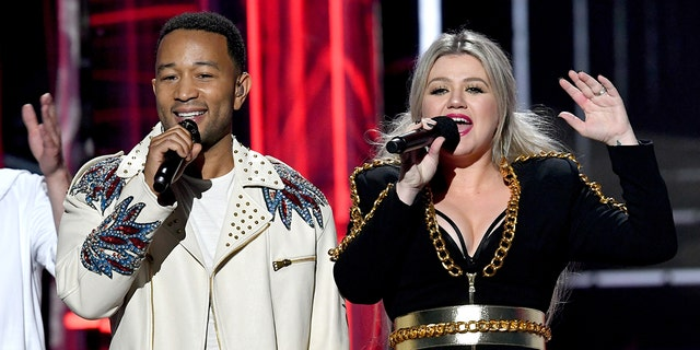 Recording artist John Legend (L) and host Kelly Clarkson speak onstage during the 2018 Billboard Music Awards at MGM Grand Garden Arena on May 20, 2018 in Las Vegas, Nevada.