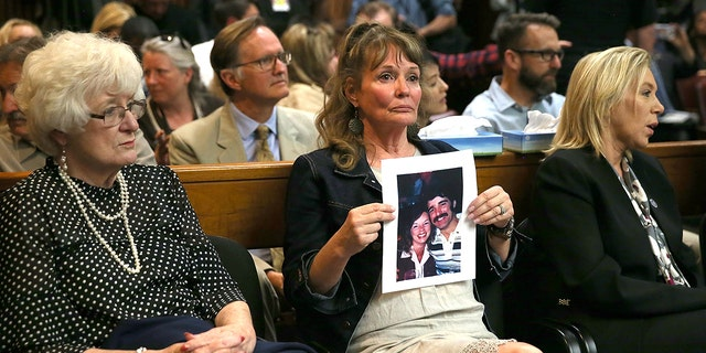 "An attendee holds a photo of Cheri Domingo and her boyfriend Gregory Sanchez, who were killed in 1981, as she sits in the courtroom during the arraignment of Joseph James DeAngelo, the suspected ""Golden State Killer"" on April 27, 2018 in Sacramento, California. (Photo by Justin Sullivan/Getty Images)"