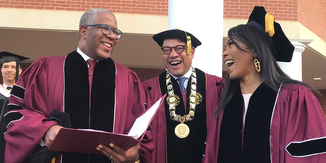 Robert F. Smith, left, laughs with David Thomas, center, and actress Angela Bassett at Morehouse College on Sunday, May 19, 2019, in Atlanta. Smith, a billionaire technology investor and philanthropist, said he will provide grants to wipe out the student debt of the entire graduating class at Morehouse College - an estimated $40 million.