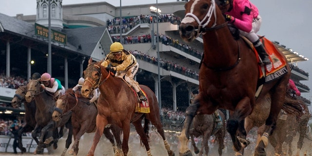 Luis Saez, in pink silks, rides Maximum Security across the finish line first against Flavien Prat, in yellow silks, on Country House in Saturday's Kentucky Derby. (AP Photo/Matt Slocum)
