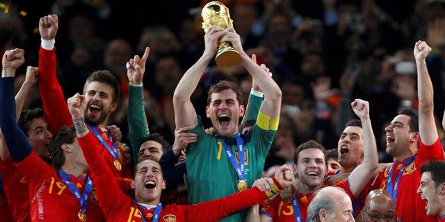 FILE PHOTO: Spain's captain Iker Casillas (C) lifts the World Cup trophy after the 2010 World Cup final soccer match between Netherlands and Spain at Soccer City stadium in Johannesburg July 11, 2010. REUTERS/Jerry Lampen/File Photo - RC1C1732E880