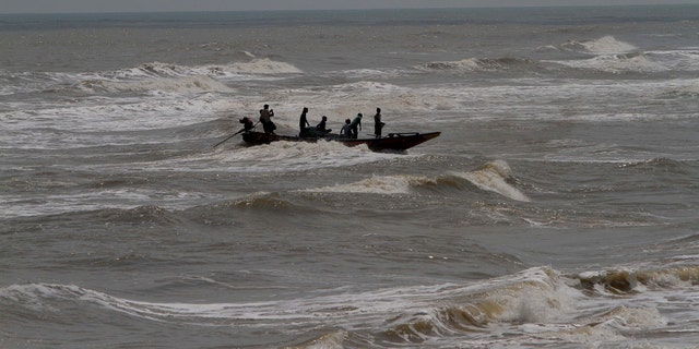 In this Wednesday, May 1, 2019 photo, Indian fishermen attempt to bring their boat ashore amid strong winds at Chandrabhaga beach in Puri district of eastern Odisha state, India.