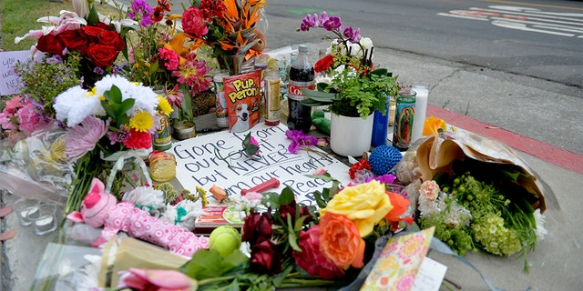 In this Wednesday, May 8, 2019, photo flowers and cards rest on a memorial for Jessica Bingaman, a popular dog walker, who was killed along with five of six dogs she was transporting in Long Beach, Calif. (Brittany Murray/The Orange County Register via AP)