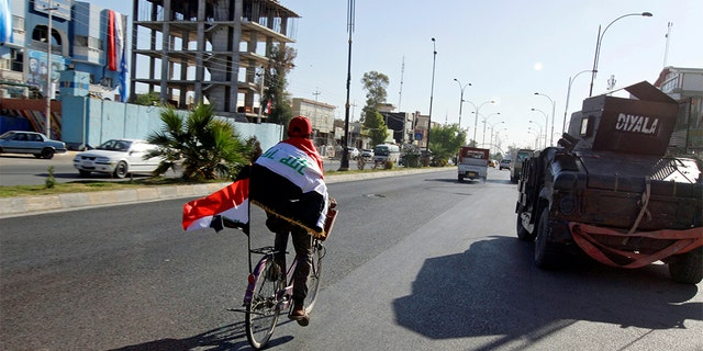 A man riding a bicycle with an Iraqi flag north of Kirkuk in October 2017. At least six explosions hit Kirkuk on Thursday, killing multiple people.