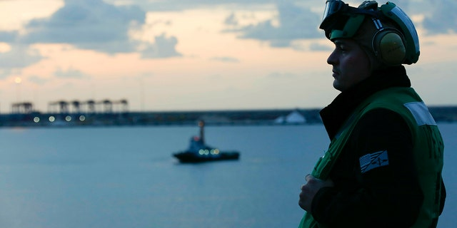 """In this Thursday, May 9, 2019 photo released by the U.S. Navy, Aviation Maintenance Administrationman 2nd Class Jason Caldwell, assigned to the """"Jolly Rogers"""" of Strike Fighter Squadron 103, observes sunrise on the flight deck of the Nimitz-class aircraft carrier USS Abraham Lincoln while transiting the Suez Canal in Egypt. (Mass Communication Specialist 3rd Class Amber Smalley, U.S. Navy via AP)"""