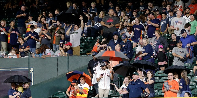Fans sitting behind right field pull out umbrellas as rain seeps through gaps in the roof of Minute Maid Park during the eighth inning of a baseball game between the Texas Rangers and the Astros on Thursday, May 9, 2019, in Houston.