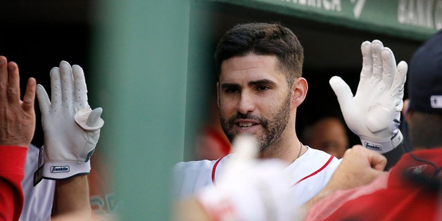 Boston Red Sox's J.D. Martinez is congratulated in the dugout after hitting a home run during the eighth inning of a baseball game against the Cleveland Indians, Monday, May 27, 2019, in Boston. (AP Photo/Mary Schwalm)
