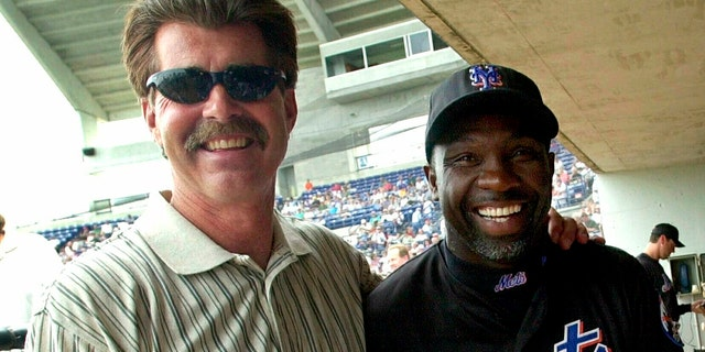 FILE - In this March 29, 2001, file photo, New York Mets coach Mookie Wilson poses with former Boston Red Sox player Bill Buckner in Port St. Lucie, Fla. (AP Photo/Ron Frehm, File)