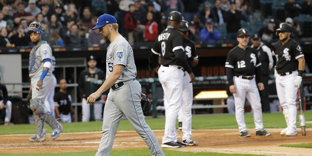 Kansas City Royals starting pitcher Glenn Sparkman, left, walks off the field after being ejected by home plate umpire Mark Carlson for hitting Chicago White Sox's Tim Anderson with a pitch during the second inning of a baseball game Wednesday, May 29, 2019, in Chicago. (AP Photo/Charles Rex Arbogast)