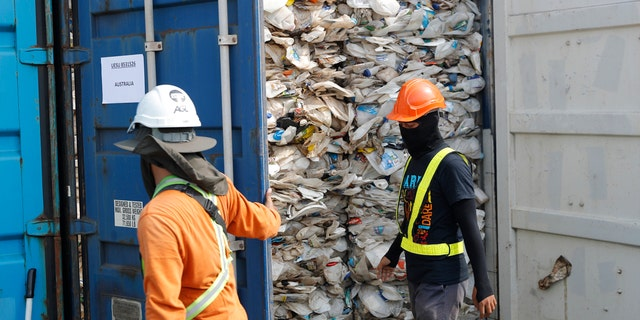 Workers open a container full of non-recyclable plastic detained by authorities at the west port in Klang, Malaysia, Tuesday, May 28, 2019. (AP Photo/Vincent Thian)